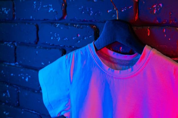 Wit unisex t-shirt in neonlicht, kopie ruimte