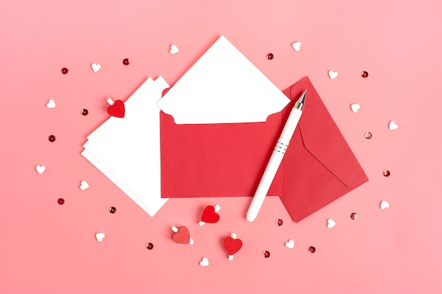 Wit vel papier, rode envelop, geschenkdoos, tittle sparkles, pen op roze achtergrond
