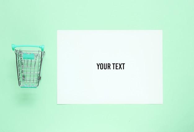 Wit vel papier voor kopie ruimte, mini winkelwagentje op groene achtergrond. creatieve winkelachtergrond