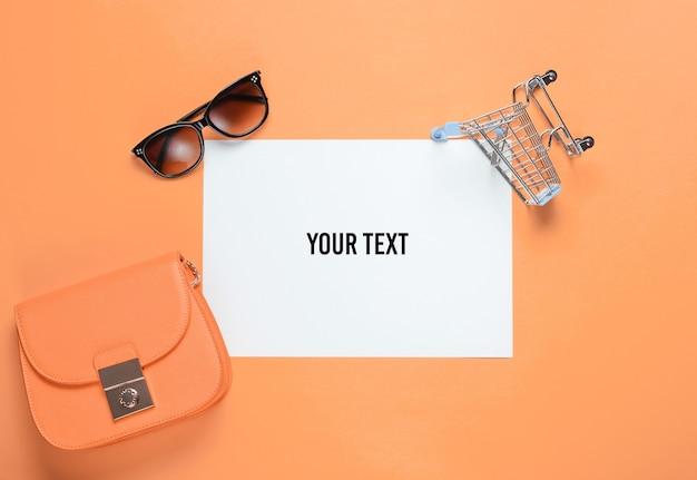Wit vel papier voor kopie ruimte, mini winkelwagentje, tas, zonnebril op gele achtergrond. creatieve winkelachtergrond