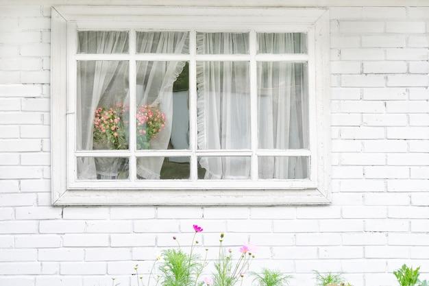 Wit venster met boeket bloemen, witte bakstenen muur