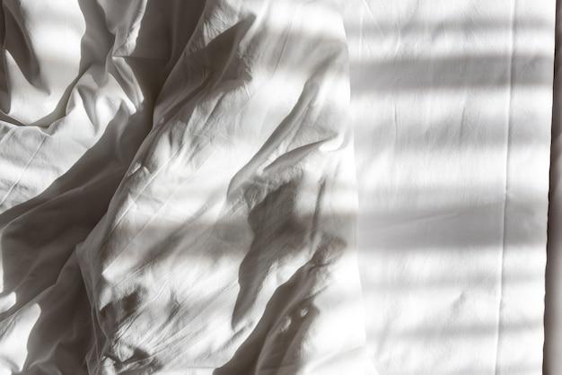 Wit verfrommeld laken, schaduw gemaakt door kussen of deken. ochtend en wakker worden thuis of in hotel, motel of hostel. onopgemaakt bed, katoenen doek en zacht textiel. verfrommeld dekbed en kussen
