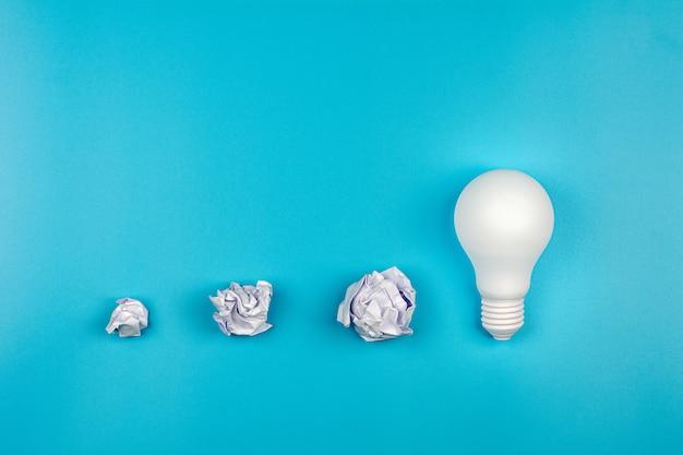 Wit verfrommeld papier en gloeilamp op blauwe tafel. - bedrijfsgroei en geweldig ideeënconcept.
