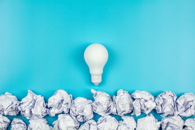 Wit verfrommeld papier en gloeilamp op blauwe tafel. - geweldig ideeënconcept.
