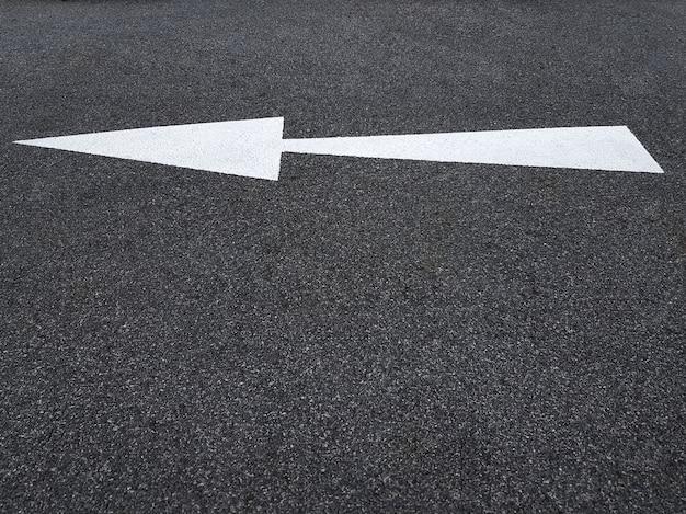 Wit verkeerspijlsymbool op asfaltweg die naar links wijst