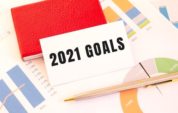Wit visitekaartje met tekst 2021 goals ligt naast rode visitekaarthouder. financieel concept.
