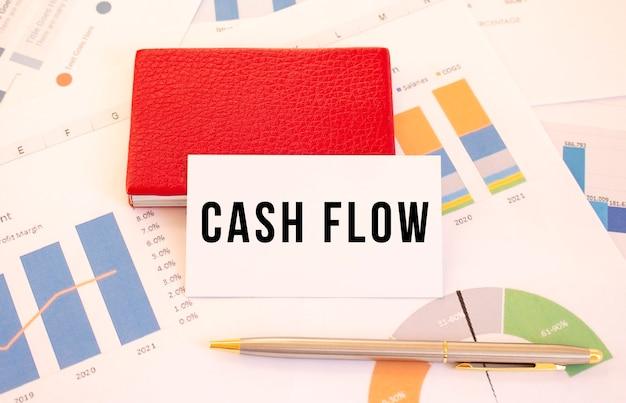 Wit visitekaartje met tekst cash flow ligt naast rode visitekaarthouder. financieel concept.