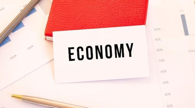 Wit visitekaartje met tekst economie ligt naast rode visitekaarthouder