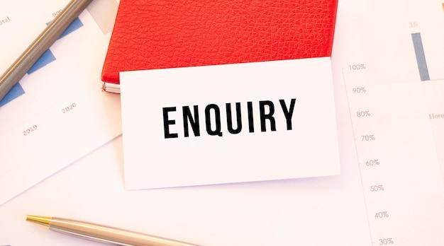 Wit visitekaartje met tekst onderzoek ligt naast rode visitekaartjehouder. financieel concept.