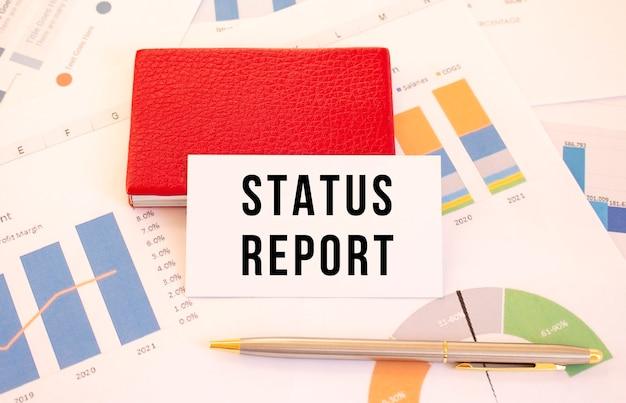 Wit visitekaartje met tekst status report ligt naast rode visitekaarthouder. financieel concept.