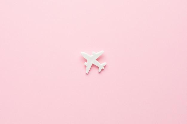 Wit vliegtuig in een minimale stijl op roze, bovenaanzicht