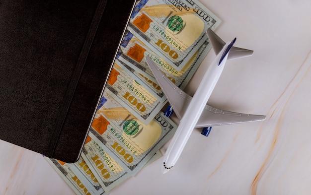 Wit vliegtuig landt op bankbiljetten van het meest dominante geld in de amerikaanse dollar van de wereld