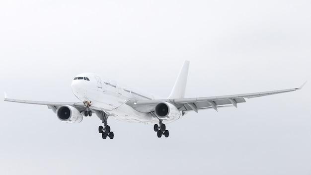 Wit vliegtuig met chassis in de lucht die voor landing voorbereiden