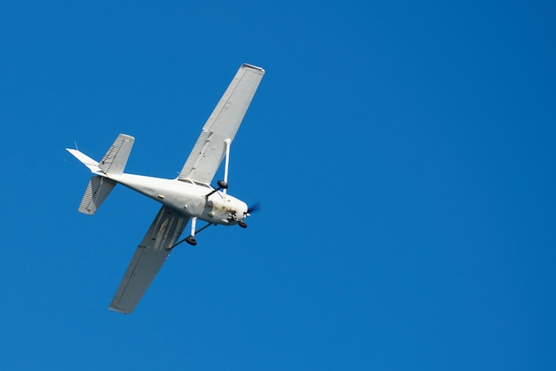 Wit vliegtuigje, geroest op de bodem, een draai in de lucht in san diego