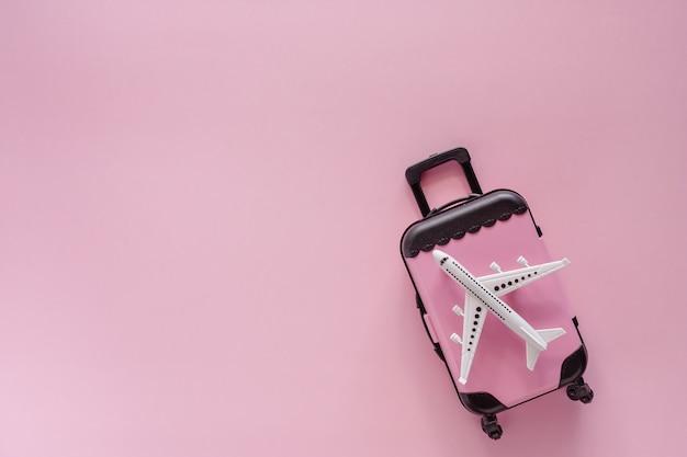Wit vliegtuigmodel met pinkbagage op roze achtergrond voor reis en reis