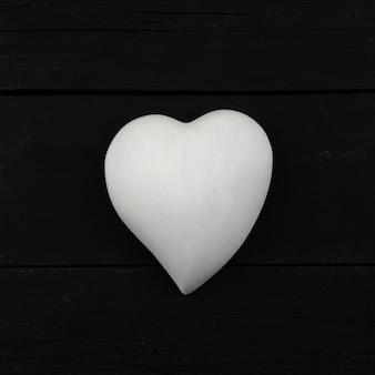 Wit volumetrisch hart op een zwarte natuurlijke houten achtergrond