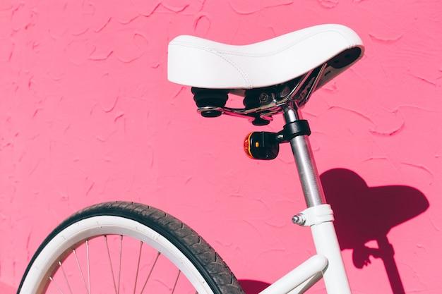 Wit zadel van een vrouwelijke stadsfiets tegen een achtergrond van een roze muur