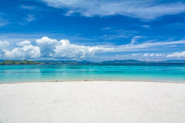 Wit zand strand met twee verschillende kleuren van clearblue zee op kanawa island, komodo