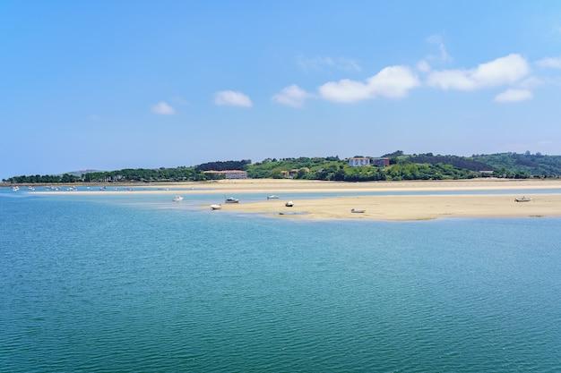 Wit zandstrand met kleine boten en blauwe lucht in de zomer