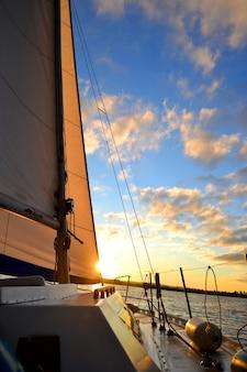 Wit zeiljacht wit tegen de blauwe lucht met wolken en zon bij zonsondergang