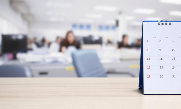 Witboek bureaukalender op houten tafelblad met wazig kantoor interieur achtergrond afspraak en zakelijke bijeenkomst concept