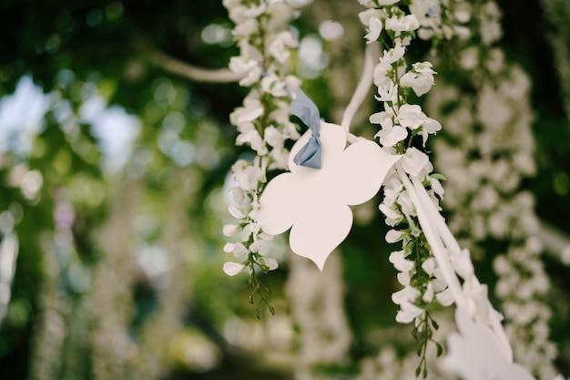 Witboek decoratieve bloem die op een lint tegen een oppervlakte van wit blauweregenhuwelijk hangen