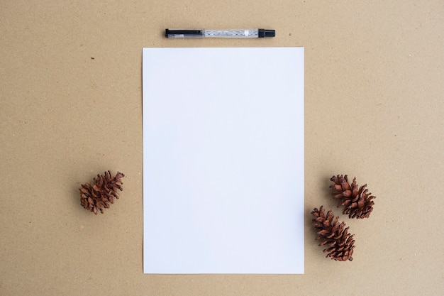 Witboek, dennenboombloemen en pen op bruine papieren achtergrond. minimalistische stijl