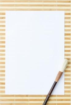 Witboek met een penseel op een bamboemat