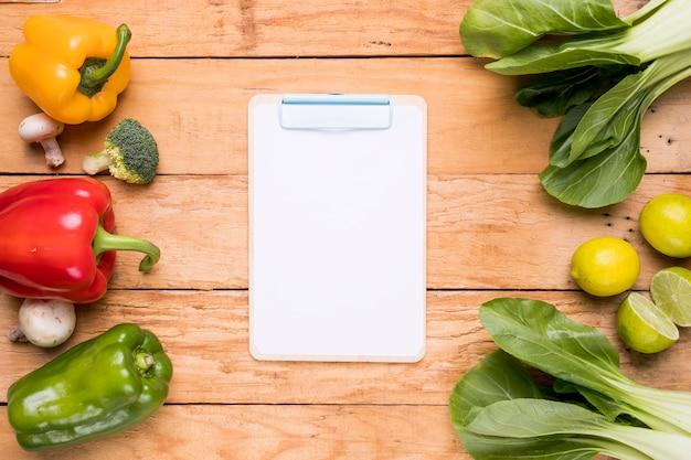 Witboek op klembord dichtbij de groene paprika's; broccoli; paddestoel; bokchoy en citroen op houten bureau