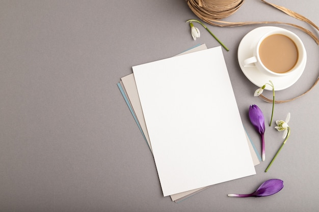 Witboek vel mockup met krokus en galanthus bloemen en kopje koffie