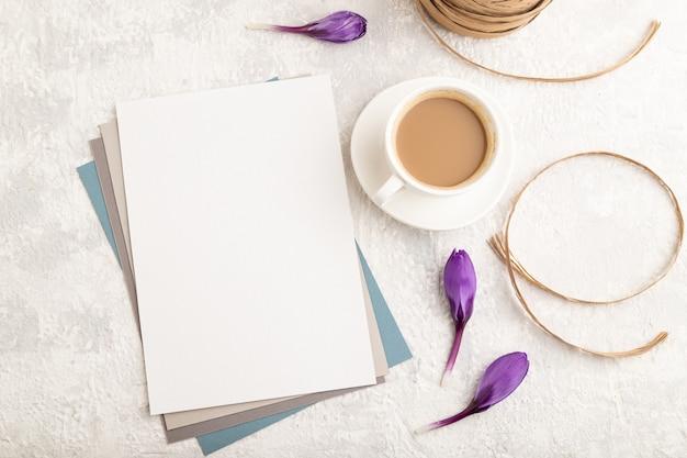 Witboek vel mockup met lentekrokus bloemen en kopje koffie op grijze betonnen achtergrond.