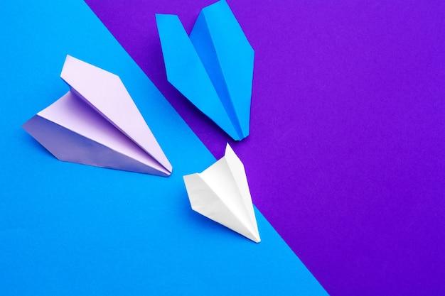Witboek vliegtuig op een blauwe en paarse papieren achtergrond