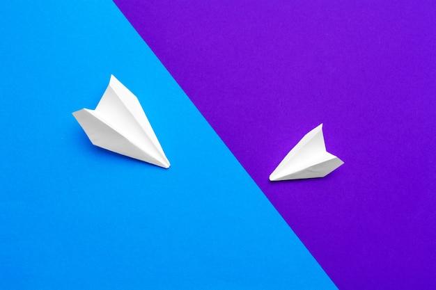 Witboek vliegtuig op een kleurblok blauwe en paarse achtergrond