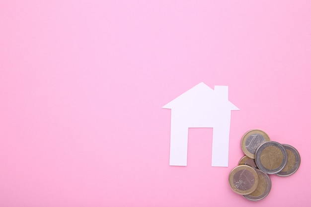 Witboekhuis met muntstukken op roze achtergrond