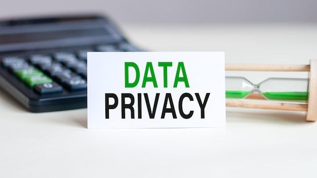 Witboekkaart met tekst data privacy, rekenmachine en zandloper achter