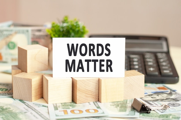 Witboekkaart met tekstwoorden van belang op de houten blokken. bankbiljetten, zwarte rekenmachine en groene plant op de achtergrond. bedrijfsconcept.