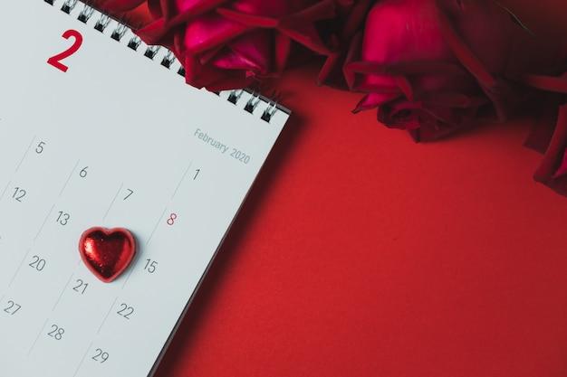 Witboekkalender en rode roos geplaatst op een rode tafel, bovenaanzicht en kopie ruimte, valentijnsdag thema