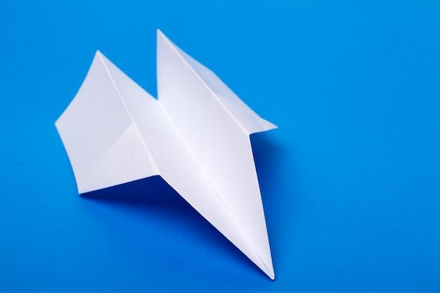 Witboekvliegtuig over een blauwe achtergrond.