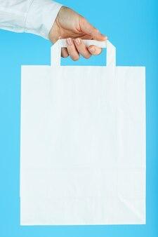 Witboekzak at arm's length geïsoleerd op een blauwe achtergrond. lay-out van de verpakkingssjabloon met ruimte voor kopiëren, adverteren.