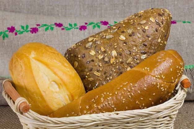 Witbrood, broodjes bestrooid met pitjes, in een rieten mand stokbrood