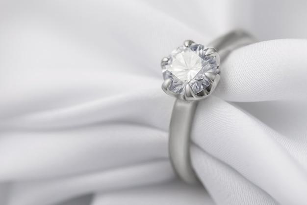 Witgouden ring met een diamant op een zijden stof