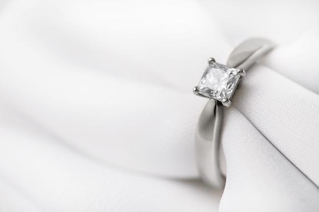 Witgouden trouwring met een grote diamant op een zijden stof
