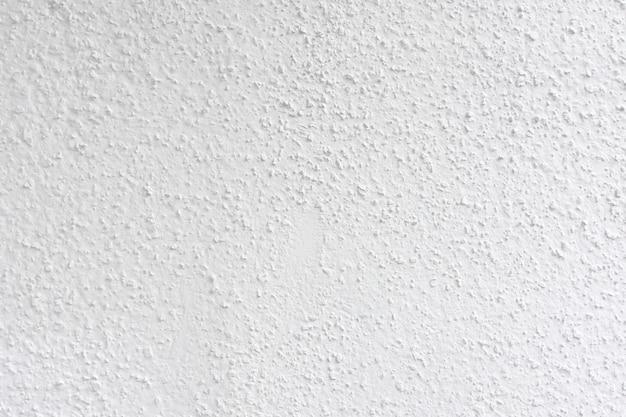 Witgrijs geschilderde cementmuur, oneffen betonnen oppervlak