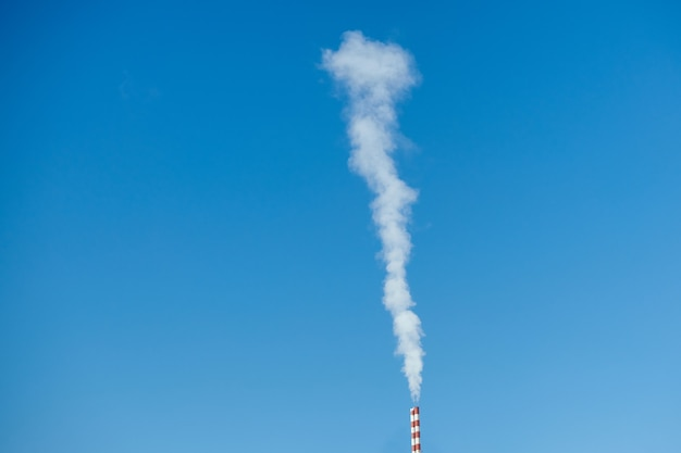 Witgrijze rook vervuilt op zonnige dagen door de schoorsteen in de blauwe lucht