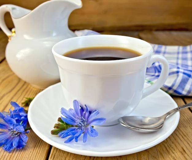 Witlofdrankje in een witte kop met een bloem op een schoteltje en een lepel