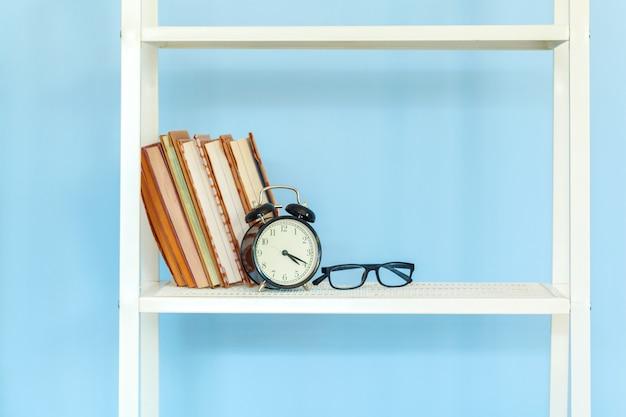 Witmetaalrek met boeken tegen blauwe achtergrond