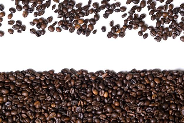 Witte achtergrond met koffiebonen aan de zijkant. bovenaanzicht. stilleven. ruimte kopiëren. plat leggen.