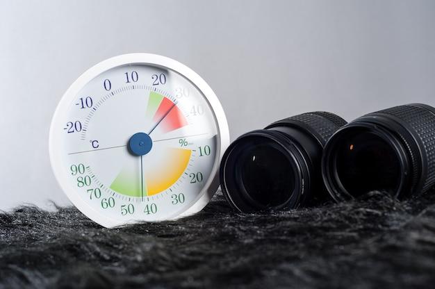 Witte analoge thermometer en hygrometer met fotoapparatuur.