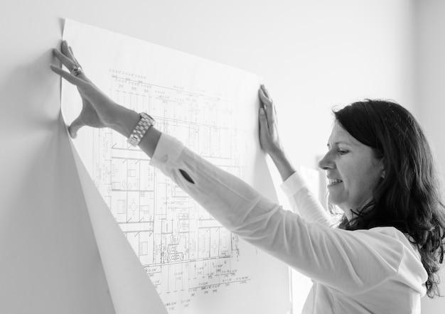 Witte architect die bouwplan op witte muur toont