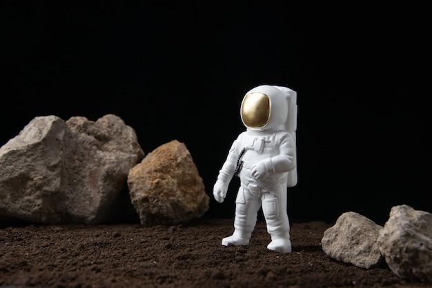Witte astronaut op de maan met rotsen op de donkere fantasy-sci-fi